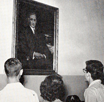 A photograph of students of Charles L. Coon High School in Wilson County looking at a portrait of Coon from the 1950 school yearbook. Image from the Wiilson County Public Library.