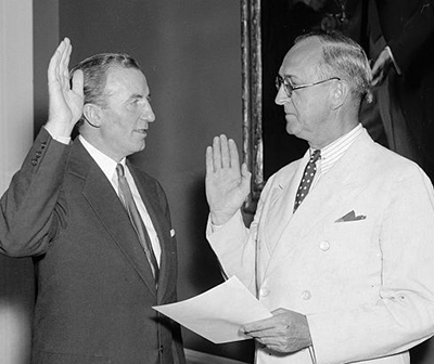 "Harris & Ewing. ""Hanes [left] takes oath as Assistant Secretary of Treasury. Washington, D.C., July 1. John W. Hanes, former New York broker and member of the S.E.C., pictured taking the oath of office today as Assistant Secretary of The Treasury from Frank Birgfeld, Chief Clerk ..."". Photograph. July 1, 1938. LC-H22-D- 4206. Prints and Photographs Division, Library of Congress."