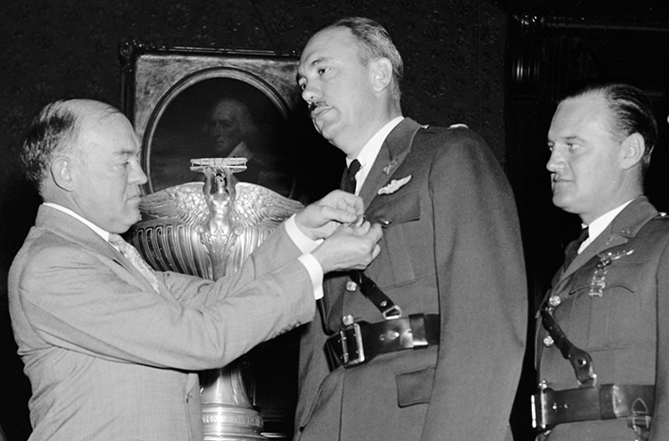 "War Secretary Harry H. Woodring (left) pins medals on Carl J. Crane (center) and George V. Holloman (right). Harris & Ewing. ""War Secretary presents Army Flyers with Mackay Trophy. Washington, D.C., Oct. 14. As a reward for their development and demonstration of the original automatic landing device for aircraft, Captains Carl J. Crane and George V. Holloman, U.S. Army Air Corps, were today presented with the MacKay trophy for 1937 by Secretary of War Harry H. Woodring. Gold medals, emblematic of the trophy were presented the Flyers at the same time. Left to right: Charles F. Horner, Chairman of the National Aeronautic Association; Secretary Woodring, Capt. Carl J. Crane, and Capt. George V. Holloman, 10/14/38"". Photograph. [19]38 October 14. LC-H22-D- 4701. Prints and Photographs Division, Library of Congress."
