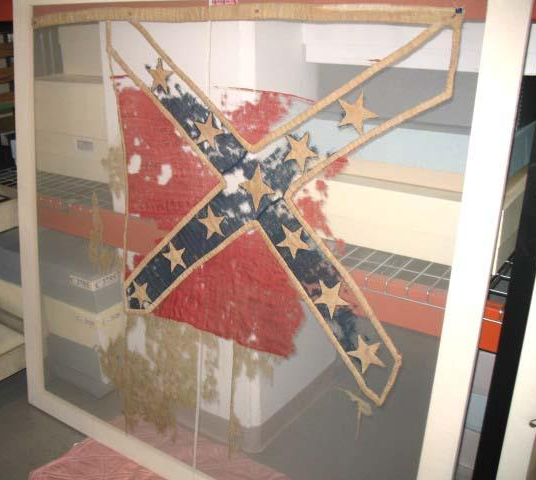 Photograph of surviving fragments of the Confederate Flag of the North Carolina 17th Regiment, reported to have been secretly saved and conveyed to saftey by Thomas Abel and at some ponit into the hands of  Wilson G. Lamb.  The artifact was dispalyed in the North Carolina Hall of History on May 20, 1895 and donated by Lamb to the museum on November 28, 1914.  Item H.1914.2601. from the collections of the North Carolina Museum of History.  Used courtesy of the North Carolina Department of Cultural Resources.