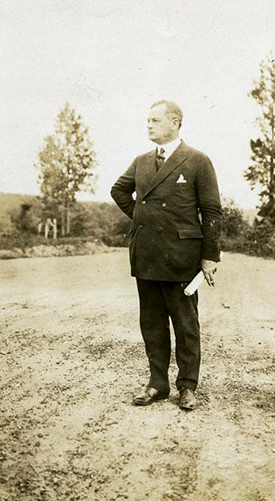 Governor Angus Wilton McLean, standing on an unpaved road, 1925-1929. Image from the North Carolina Museum of History.
