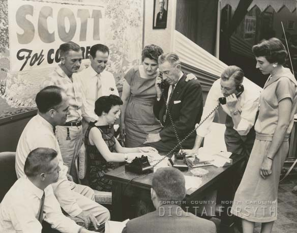 """Ralph Scott headquarters for his congressional renomination, 1958. Mr. Scott is the man on the left talking on the telephone. His wife stands beside him. Mr. Scott won the renomination election,"" from Digital Forsyth, published 1958 by Forsyth County Public Library. Presented on Digital Forsyth."