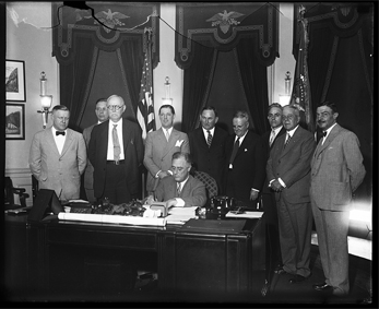 Photograph of President Franklin Roosevelt (FDR) signing the Small Home Loan Measure, 1933, by Harris & Ewing.  From the Harris & Ewing Collection, Library of Congress Prints & Photographs Online Catalog. William F. Stevenson, Chairman of the Home Loan Bank Board, is listed among those seen in the photograph.