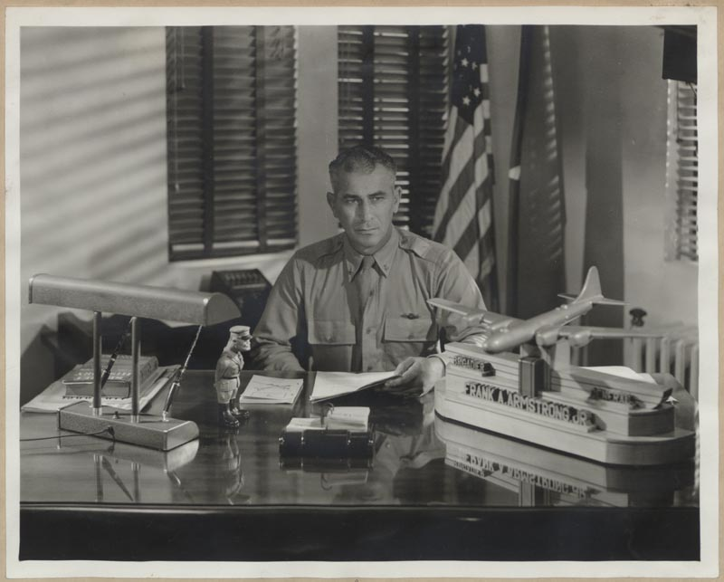 "General Frank Armstrong seated at desk in office at Grand Island Army Airfield in Nebraska. Commanding General of 315th Bomber Wing of B-29s. Model plane on desk includes inscription ""Brigadier General Frank A. Armstrong, Jr."" 1944. From East Carolina Digital Collections."
