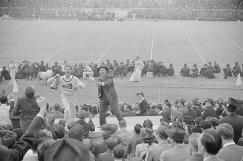 Kay Kyser and cheerleader cheering for North Carolina team at Duke University-North Carolina football game. Durham, North Carolina. Courtesy of the Library of Congress.