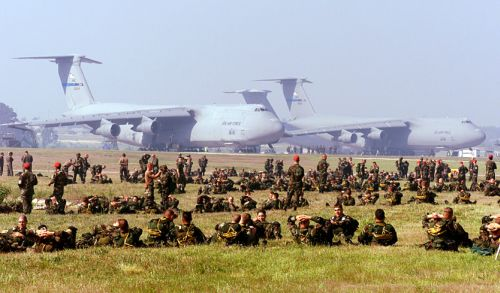""" 	   Soldiers of the U.S. Army's 82nd Airborne Division relax at Pope Air Force Base, N.C., prior to loading into aircraft for an airdrop on May 7, 2000."" Image courtesy of the U.S. Department of Defense."
