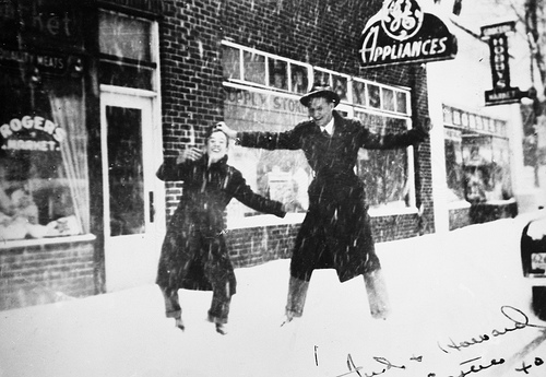 Fred and Howard (last names not known) on corner of Chatham and Academy Streets, in front of Hobby's Appliance Store, Cary, NC, during snow of Easter 1940. From the General Negative Collection, North Carolina State Archives, call # N_2000_4_4.