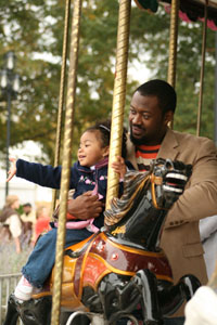 Father and daughter on carousel at the State Fair. Image courtesy of the NC State Fair: http://www.ncstatefair.org/