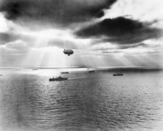 A U.S. Navy blimp protects an Atlantic convoy in 1943. During World War II, Weeksville was a base for blimps that patrolled the Atlantic Ocean off the coasts of North Carolina and Virginia for German submarines. National Archives (neg. 65729, U.S. Navy).
